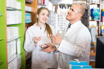 Professional pharmacist standing at pay desk