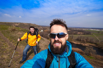 hipster young friends taking selfie on a hill in the campaign, c