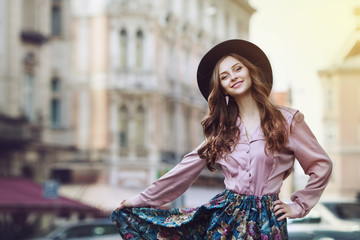 Outdoor portrait of a young beautiful fashionable happy lady posing on a street. Model wearing stylish clothes. Girl looking at camera. Female fashion. City lifestyle. Copy space. Toned
