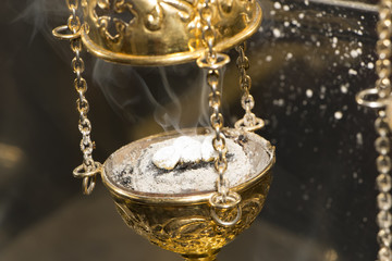 Brass thurible liturgy censer with burning incense in it