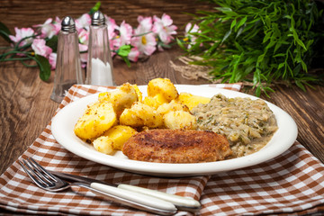 Delicious meal of minced meat cutlet, potatoes and fried cabbage