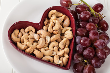 Cashews in a heart shaped bowl with red seedless grapes on white plate
