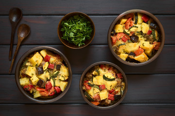 Baked potato, eggplant, zucchini and tomato casserole in rustic bowls, photographed overhead on dark wood with natural light