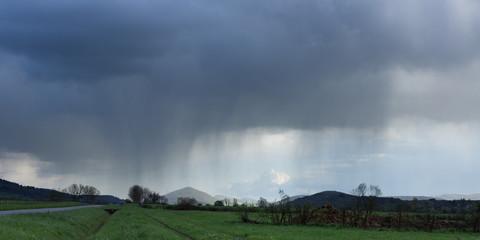 Un paysage de campagne au bord d'une route avec des nuages libérant la pluie au loin