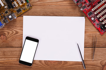 Top view on bright wooden office desk with paper, pen, smartphone with blank screen, cup off coffee and other office equipment.