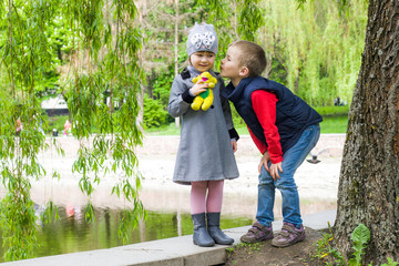 Boy is kissing cute girl with a toy