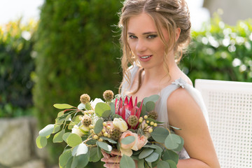 beautiful young bride on a lawn poses for photo