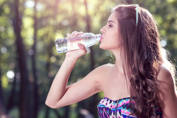 Girl drinking water from bottle in nature
