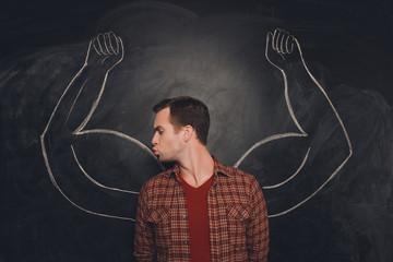 Attractive young  man kissing his drawn biceps