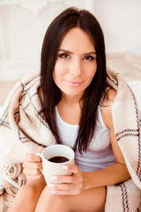 Pretty young woman  basking with hot coffee  and plaid blanket