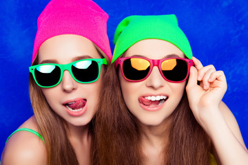 Portrait of two pretty sisters in hats and glasses showing tongu