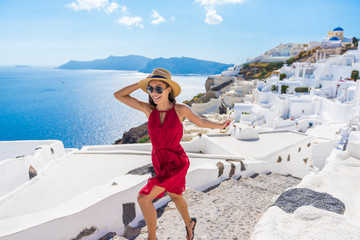 Wall Mural - Travel Tourist Happy Woman Running Stairs Santorini, Greek Islands, Greece, Europe. Girl on summer vacation visiting famous tourist destination having fun smiling in Oia.