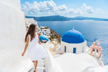 Wall Mural - Santorini travel tourist woman on vacation in Oia walking on stairs. Person in white dress visiting the famous white village with the mediterranean sea and blue domes. Europe summer destination