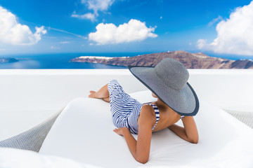 Wall Mural - Vacation travel woman relaxing enjoying Santorini looking at famous view of Caldera. Young lady lying down on sun bed sofa lounge chair on holidays. Amazing view of sea. Europe travel destination.