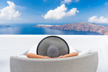Wall Mural - Travel vacation woman relaxing enjoying Santorini looking at famous view of Caldera. Young lady lying down on sun bed sofa lounge chair on holidays. Amazing view of sea. Europe travel destination.