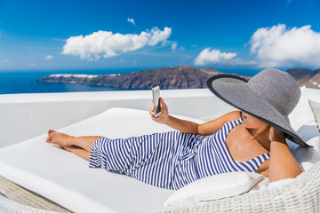 Wall Mural - Relaxing woman using smart phone while lying on couch outdoor. Beautiful female is at resort terrace. Happy tourist is spending leisure time during vacation on Santorini, Greece, Europe.