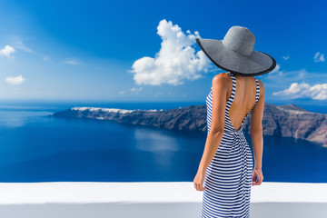 Wall Mural - Luxury travel vacation woman looking at view on Santorini famous Europe travel destination. Elegant young lady living fancy jetset lifestyle wearing dress on holidays. Amazing view of sea and Caldera.