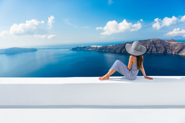 Fototapete - Europe Greece Santorini travel vacation. Woman looking at view on famous travel destination. Elegant young lady living fancy jetset lifestyle wearing dress on holidays. Amazing view of sea and Caldera
