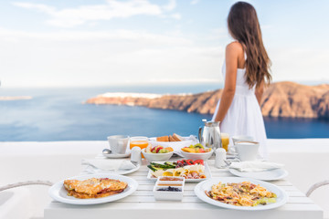 Wall Mural - Breakfast table and luxury travel woman on santorini. Well balanced perfect breakfast table served at resort. Female tourist is looking at beautiful view of sea and caldera enjoying her vacation.