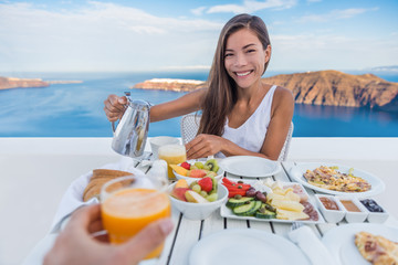 Wall Mural - Couple eating breakfast. Smiling tourist woman drinking coffee and man drinking orange juice on terrace resort outdoor. Healthy and delicious food served for breakfast.  Santorini, Greece.