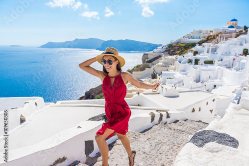 Wall mural Travel Tourist Happy Woman Running Stairs Santorini, Greek Islands, Greece, Europe. Girl on summer vacation visiting famous tourist destination having fun smiling in Oia.
