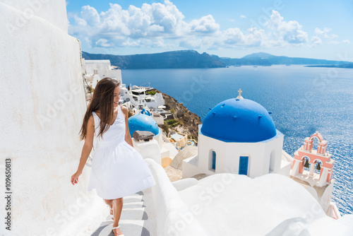 Wall mural Santorini travel tourist woman on vacation in Oia walking on stairs. Person in white dress visiting the famous white village with the mediterranean sea and blue domes. Europe summer destination