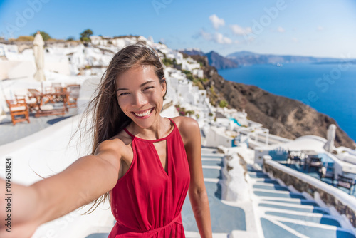 Wall mural Travel Vacation Tourist Selfie. Woman taking self-portrait photo on Santorini, Greek Islands, Greece, Europe. Girl on summer vacation visiting famous tourist destination having fun smiling in Oia.