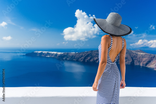 Wall mural Luxury travel vacation woman looking at view on Santorini famous Europe travel destination. Elegant young lady living fancy jetset lifestyle wearing dress on holidays. Amazing view of sea and Caldera.