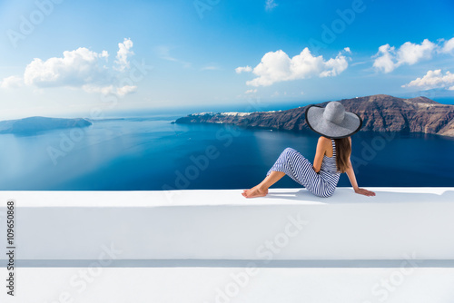 Wall mural Europe Greece Santorini travel vacation. Woman looking at view on famous travel destination. Elegant young lady living fancy jetset lifestyle wearing dress on holidays. Amazing view of sea and Caldera