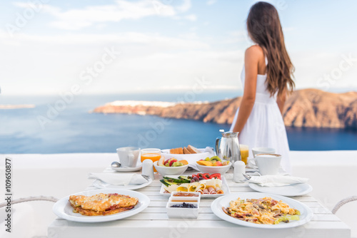 Wall mural Breakfast table and luxury travel woman on santorini. Well balanced perfect breakfast table served at resort. Female tourist is looking at beautiful view of sea and caldera enjoying her vacation.