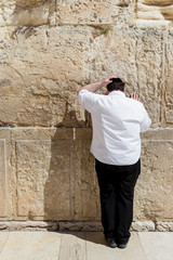 JERUSALEM, ISRAEL - MARCH 15, 2016: Man praying at the men's section of the Wailing (Western) Wall in the old town Jerusalem (Israel)