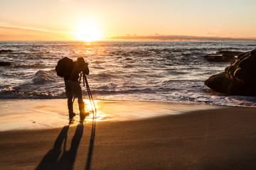 A photographer taking a picture of the ocean and rock formations with the sun low on the horizon.