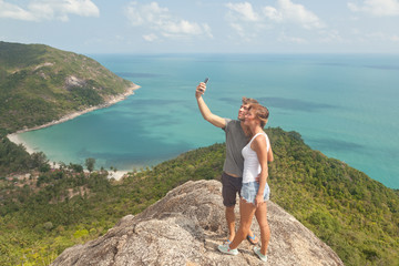 young couple of travelers  is doing selfie on a hill overlooking
