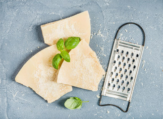 Cuts of Parmesan cheese with metal grater and fresh basil over concrete textured background
