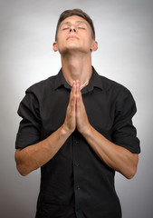 Closeup portrait young man praying hoping for best asking for forgiveness or miracle isolated gray wall background.