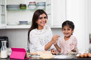 Portrait of cheerful mother and her kid in kitchen