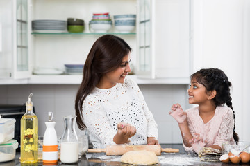 Indian mother and daughter playing while cooking