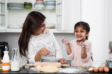 Playful little girl cooking with her mother