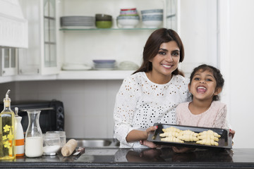 Indian mother and daughter showing tray with croissants