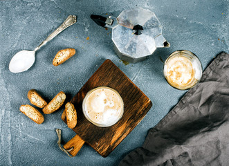 Glasses of coffee with ice cream on rustic wooden board, steel Italian Moka pot over grey concrete textured background