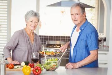 Portrait of happy senior couple preparing food