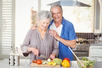 Happy senior man standing with woman cutting salad