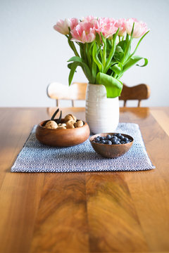 Snacks and flowers in vase on the  wooden dining table. Selective focus on blueberries.
