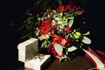 Wdding rings in gift box and bouquet on the table