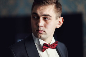 Fiance with red bow tie looks seriously