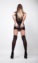young fashion woman in high heels, studio shot. woman in a short black skirt and a transparent top. she clings to her ass, back view
