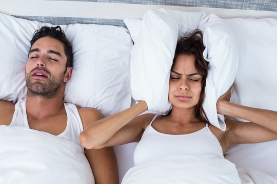 Woman blocking ears while man snoring on bed