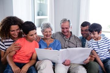 Happy family sitting on sofa and looking at photo album