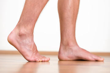 Pair of clean male feet without any illness making a step.