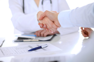 Doctor and patient handshaking. Hands close-up